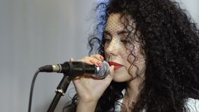 Beautiful curly brunette with veil on face sings in microphone stock video footage