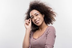 Beautiful curly dark-haired office worker wearing glasses smiling broadly royalty free stock image