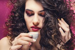 Beautiful curly girl with colourful manicure drinking from a very small cup royalty free stock photography