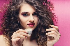 Beautiful curly girl with colourful manicure drinking from a very small cup royalty free stock photo