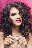 Beautiful curly girl with colourful manicure smile and drink from a small cup stock photo