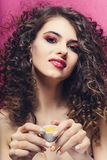 Beautiful curly girl with colourful manicure smile and drink from a small cup royalty free stock images
