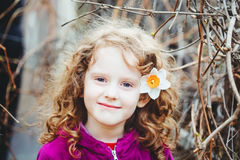 Beautiful curly girl with a flower in her hair. Background toned Stock Images