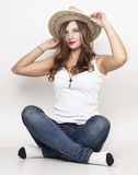 Beautiful curly girl in jeans, white t-shirt and cowboy hat. Beautiful curly girl in jeans, white t-shirt and cowboy hat Stock Photo