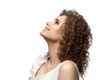 Beautiful curly girl looking up and smiling, isolated on white background. Stock Photos