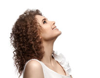 Beautiful curly girl looking up and smiling,  on white background. Royalty Free Stock Images