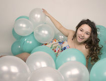 Beautiful curly girl in a  multi-colored dress playing with balloons Stock Photos