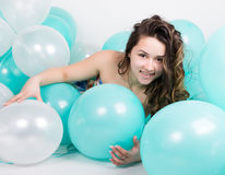 Beautiful curly girl in a multi-colored dress playing with balloons Stock Photography