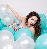 Beautiful curly girl in a multi-colored dress playing with balloons Royalty Free Stock Photo