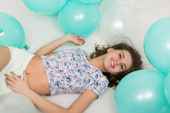 Beautiful curly girl in multi-colored top, white shorts and bright shoes playing with balloons Royalty Free Stock Photography