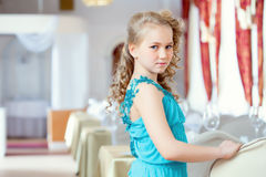 Beautiful curly girl posing in elegant blue dress Royalty Free Stock Photos