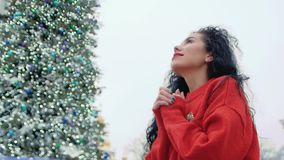 Woman holds hands in hope. Beautiful curly girl in a red sweater stands on the background of a large Christmas tree with lights. Young pretty woman holds hands stock video