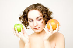 Beautiful curly girl with two fruits Royalty Free Stock Photo