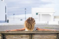 Free Beautiful Curly Hair Black Skin Tanned Woman Viewed From Back Sitting On A Bench Royalty Free Stock Photos - 141279668