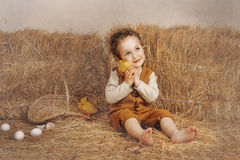 Beautiful curly-haired boy sitting next to a hay duckling ear Stock Image