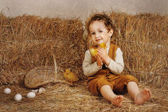 Beautiful curly-haired boy sitting next to a hay duckling in han Stock Image
