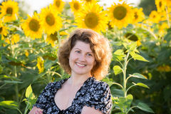 Beautiful curly-haired woman in field of sunflowers royalty free stock photography
