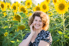 Beautiful curly-haired woman in field of sunflowers Royalty Free Stock Images