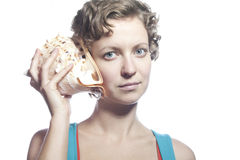 Girl with a cockleshell. The beautiful curly-headed girl holds two cockleshells near ears and listens Stock Photos