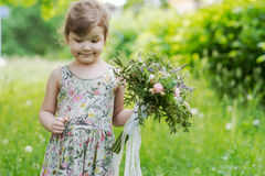 Beautiful curly little girl with  bouquet in the. Beautiful bouquet with lace and ribbons in the hands of a little girl Royalty Free Stock Images