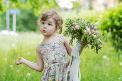 Beautiful curly little girl with  bouquet in the. Beautiful bouquet with lace and ribbons in the hands of a little girl Royalty Free Stock Photo