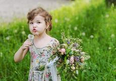 Beautiful curly little girl with  bouquet in the. Beautiful bouquet with lace and ribbons in the hands of a little girl Stock Photos