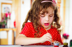 Beautiful curly little girl painting Stock Photo