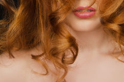 Beautiful curly long red hair on the face of woman Royalty Free Stock Image