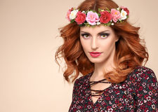 Beautiful Curly Redhead in Fashion Flower Wreath. Fashion Beautiful Curly Redhead Portrait in Flower Wreath. Shiny Curly flower fashion Volume Hairstyle. Happy stock image
