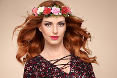Beautiful Curly Redhead in Fashion Flower Wreath. Beautiful Curly Redhead Portrait in Fashion Flower Wreath. Shiny Curly flower Volume Hairstyle. Happy Beauty stock photography