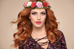 Beautiful Curly Redhead in Fashion Flower Wreath. Beautiful Curly Redhead Portrait in Fashion Flower Wreath. Shiny Curly flower Volume Hairstyle. Happy Beauty stock images