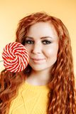 Beautiful curly redhead woman holding a red white lollipop and smiling. Beautiful curly redhead woman holding a red white lollipop looking at the camera and stock photography