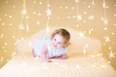 Beautiful curly toddler girl between Christmas lights Stock Photography