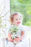 Beautiful curly toddler girl holding first spring flowers Royalty Free Stock Photography