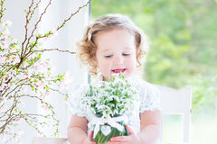 Beautiful curly toddler girl holding first spring flowers Stock Image