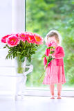 Beautiful curly toddler girl playing with peony flowers Stock Image