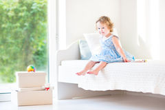Beautiful curly toddler girl sitting on a white bed Royalty Free Stock Images