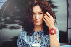 Beautiful curly woman drinking coffee near the car adjusting her hair in a blue dress Royalty Free Stock Photo