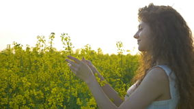 Beautiful curly woman gently touching canola flower walking in a rapeseed field stock video footage