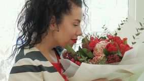 Beautiful curly woman with a gorgeous bouquet near the window stock video