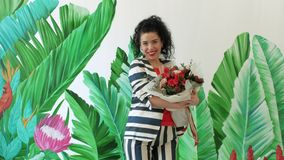 Beautiful curly woman with magnificent bouquet runs against the background of painted green leaves stock video footage