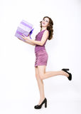 Beautiful curly woman in a short dress holding gift and looking on camera Stock Photo