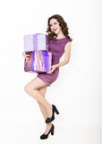 Beautiful curly woman in a short dress holding gift and looking on camera Stock Images