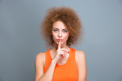 Beautiful curly woman showing silence sign Royalty Free Stock Images