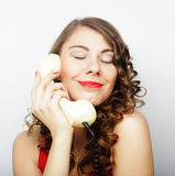 Beautiful curly woman  talking on white telephone Royalty Free Stock Photography