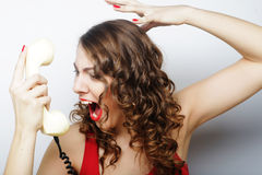 Beautiful curly woman  talking on white telephone Stock Photo