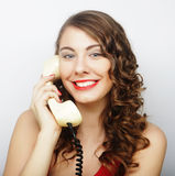 Beautiful curly woman  talking on white vintage telephone Stock Images