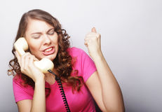 Beautiful curly woman  talking on white vintage telephone Stock Photography