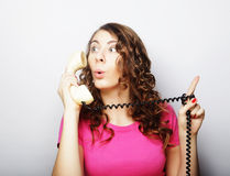 Beautiful curly woman  talking on white vintage telephone Royalty Free Stock Image