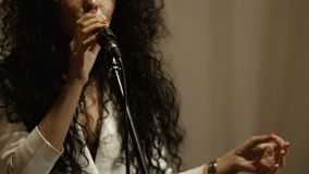 Beautiful curly woman with veil on face sings in microphone stock video footage